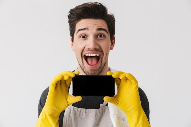 Moreno bonito moreno com avental em pé, isolado sobre o branco, mostrando o celular