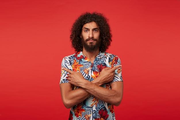 Moreno bonito severo com barba exuberante aparecendo em diferentes direções com os indicadores, franzindo as sobrancelhas enquanto olha para a câmera, isolado contra um fundo vermelho
