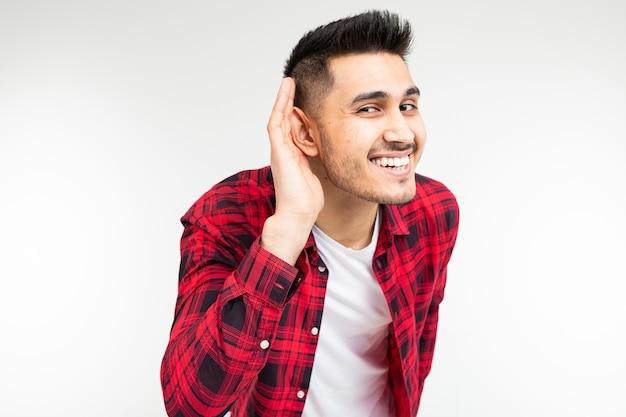 Moreno com uma camisa quadriculada escutas abertas em uma conversa sobre um fundo branco do estúdio.