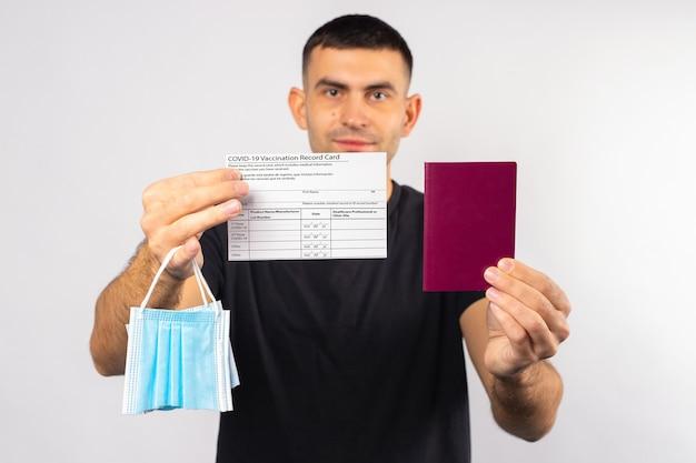 Moreno esticado na frente da câmera um passaporte de cartão de vacinação e máscara médica quebrada