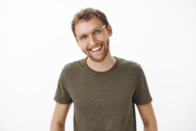 Moreno fofo e alegre, de aparência amigável, com cerdas nos óculos e uma camiseta verde-escura com a cabeça inclinada, tendo uma conversa interessante e agradável, sorrindo amplamente desfrutando de uma conversa divertida sobre a parede cinza