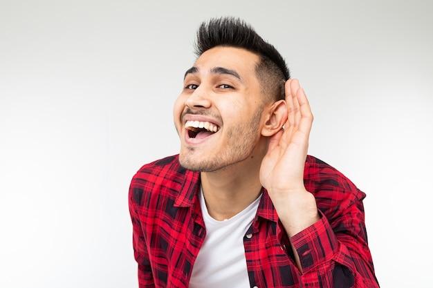 Moreno homem com uma camisa quadriculada escutas escancaradas em uma conversa sobre um fundo branco do estúdio.