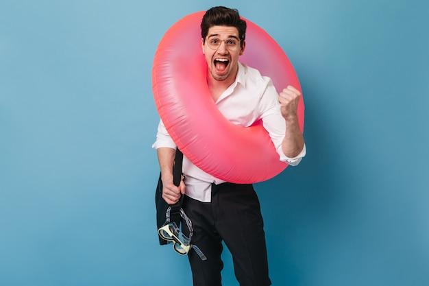 Moreno homem de calça preta e camisa branca grita com emoção e alegria. cara de óculos segura bolsa preta, máscara para nadar e coloca um círculo inflável.
