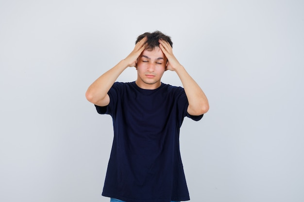 Moreno homem de camiseta escura de mãos dadas na cabeça e parecendo cansado, vista frontal.