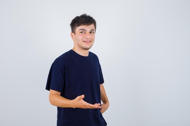 Moreno homem fingindo mostrar algo em t-shirt e olhando alegre, vista frontal.