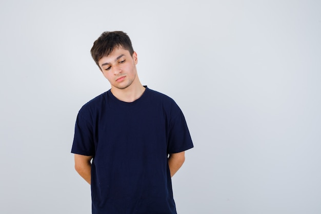 Moreno homem segurando as mãos nas costas em uma camiseta e olhando pensativo, vista frontal.