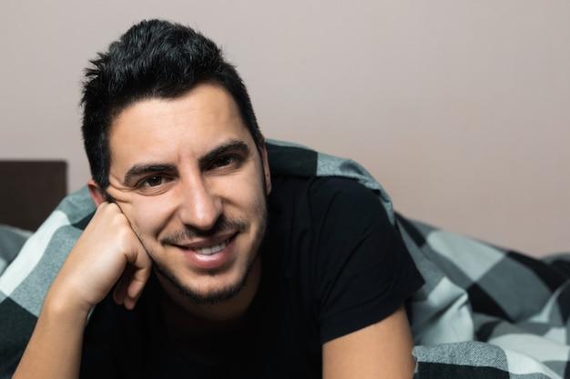 Moreno jovem bonito está deitado na cama, sorrindo e olhando
