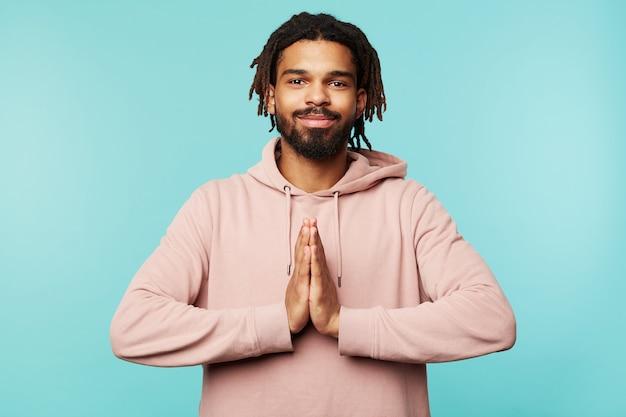 Moreno jovem positivo de olhos castanhos com dreadlocks, sorrindo agradavelmente para a câmera e levantando as mãos em um gesto de oração, em pé sobre um fundo azul
