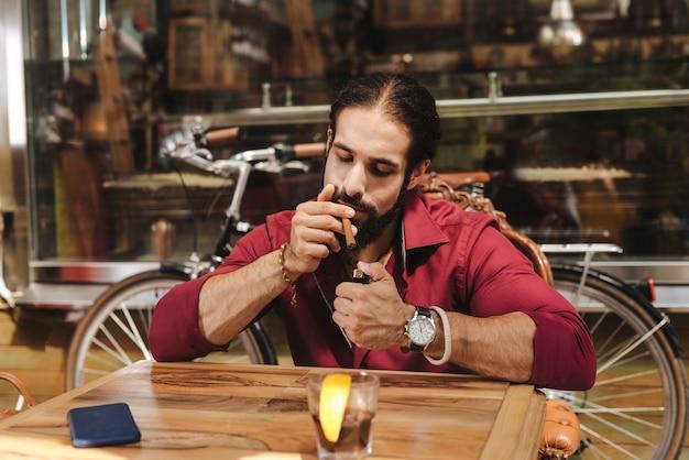 Moreno legal usando o isqueiro enquanto quer fumar um charuto