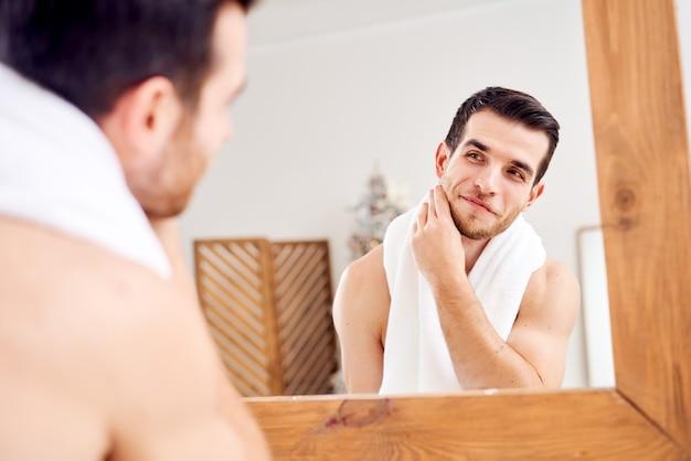 Moreno, sem barbear, sem barba, com uma toalha branca no pescoço, perto do espelho