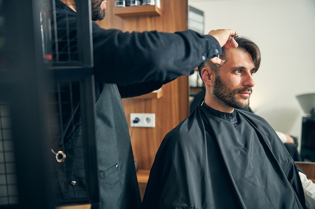 Moreno sério do sexo masculino pensando profundamente enquanto espera por um corte de cabelo estiloso