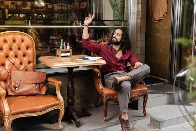 Moreno simpático ligando para o garçom enquanto está sentado no café