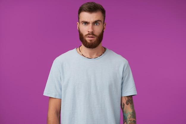 Moreno tatuado e confuso, com corte de cabelo da moda, posando em roxo com as mãos para baixo, contraindo a testa de forma atordoada e levantando a sobrancelha Foto gratuita