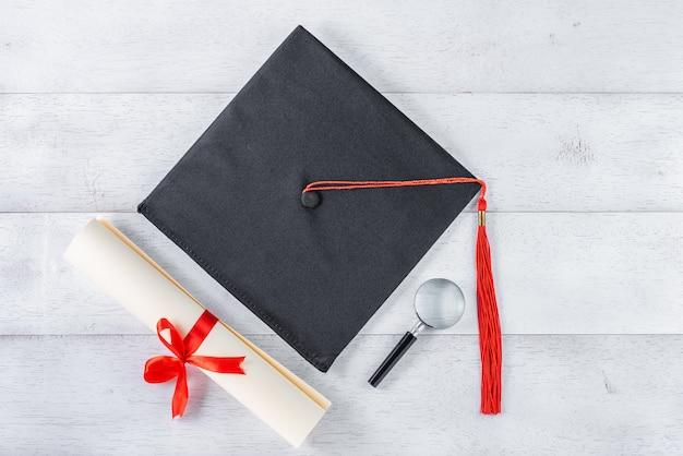 Mortarboard, lupa e diploma amarrado com fita vermelha na mesa de madeira branca, vista superior