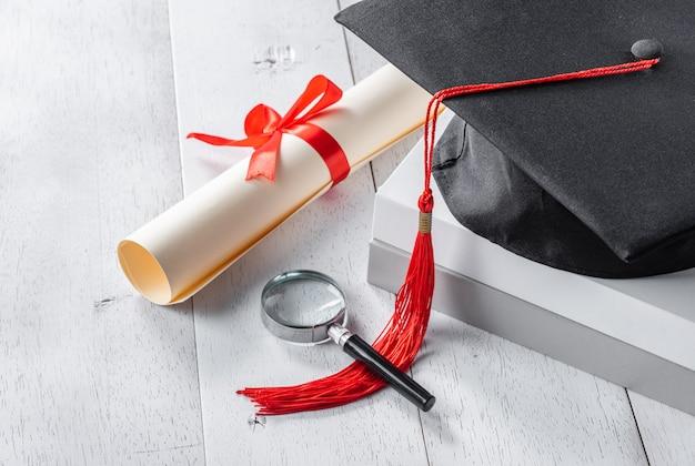Mortarboard, lupa e diploma amarrado com fita vermelha na mesa de madeira branca
