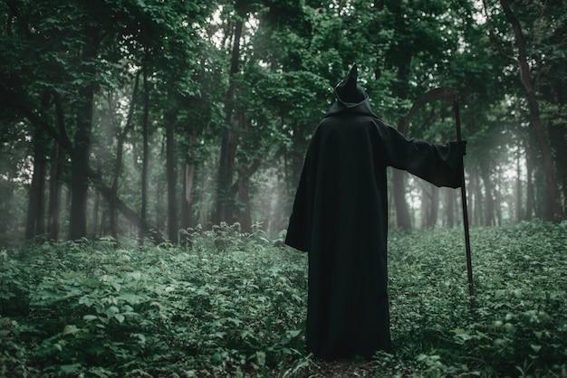 Morte em um moletom preto com uma foice na floresta