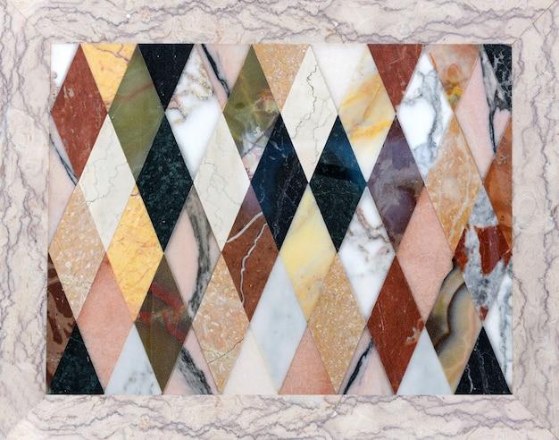 Mosaico colorido de diferentes tipos de mármore italiano em um padrão geométrico repetido de diamantes mostrando as texturas das pedras