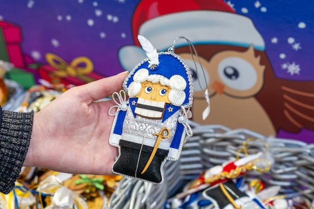 Moscou, rússia - 15 de dezembro de 2020: exposição de brinquedos no mercado de natal. decoração festiva para árvore de natal. mão de uma mulher segurando o quebra-nozes.