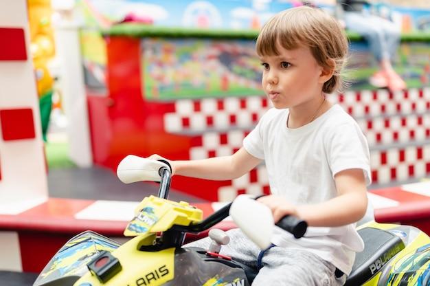 Moscou, rússia, 28 de maio de 2021 - criança feliz menino divertido andando de pequenos carros elétricos em um campo de esporte em um playground para entretenimento. crianças andando no carro de brinquedo em um parque de diversões