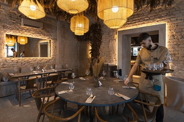 Moscou, rússia, o garçom serve a mesa com o luxuoso interior do restaurante com lustre ...