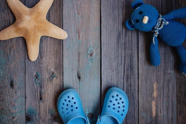 Moscovo, rússia - 05.28.2018: chinelos de praia do bebê, estrela do mar, urso de pelúcia em fundo de madeira