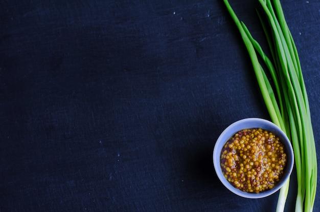 Mostarda de dijon em um prato de molho pequeno com cebolinha na ardósia preta