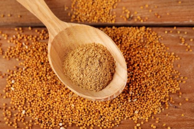 Mostarda em pó em colher de pau em sementes de mostarda, em madeira