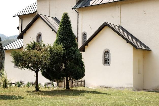 Mosteiro branco e fundo religioso de árvores verdes