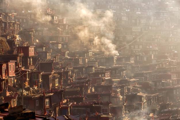 Mosteiro de vista superior em larung gar (academia budista) em um tempo de manhã quente e nevoenta, sichuan, china