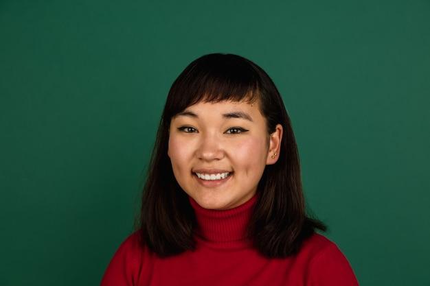 Mostra a tela do telefone em branco. retrato de mulher bonita jovem asiático oriental sobre fundo verde com copyspace.