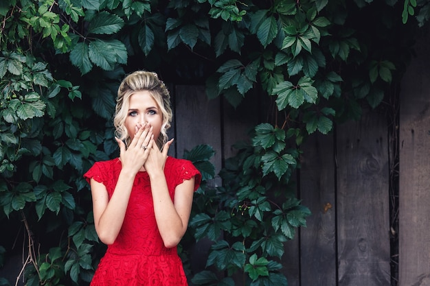 Mostra choque, susto. loira jovem atraente com um vestido vermelho cobre a boca de surpresa.