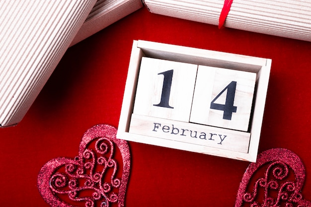 Mostra de calendário de madeira de 14 de fevereiro com coração vermelho e caixas de presente.