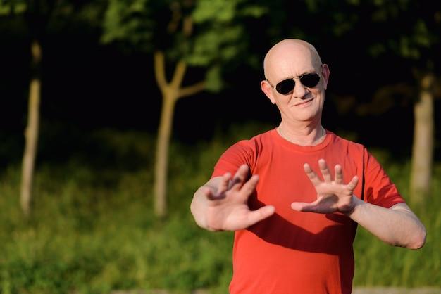 Mostra o gesto de parada da mão. velho em t-shirt vermelha ao ar livre no parque.