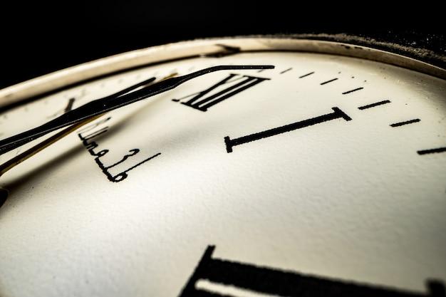 Mostrador de relógio de metal antigo em foto macro escura