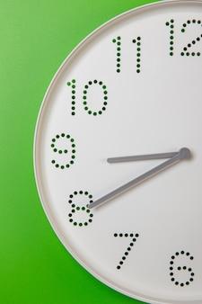Mostrador de relógio de parede com close-up dos ponteiros dos minutos e das horas