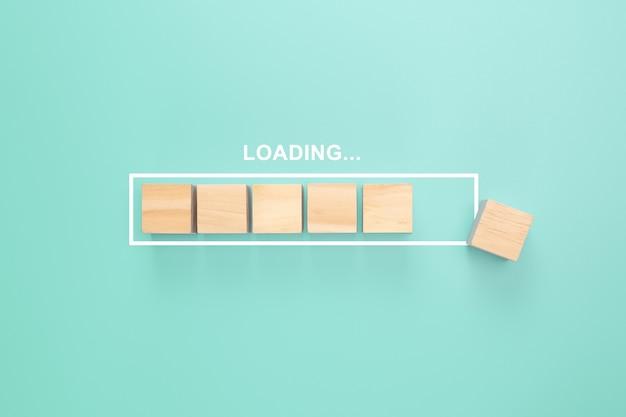 Mostrando a barra de carregamento com cubo de madeira sobre fundo azul. barra de progresso feita de cubos de madeira.
