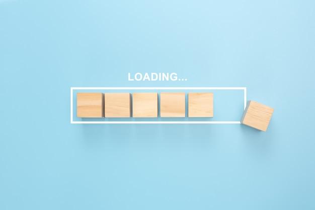 Mostrando a barra de carregamento com cubo de madeira sobre fundo azul. blocos de madeira com a palavra loading no progresso da barra de carregamento.