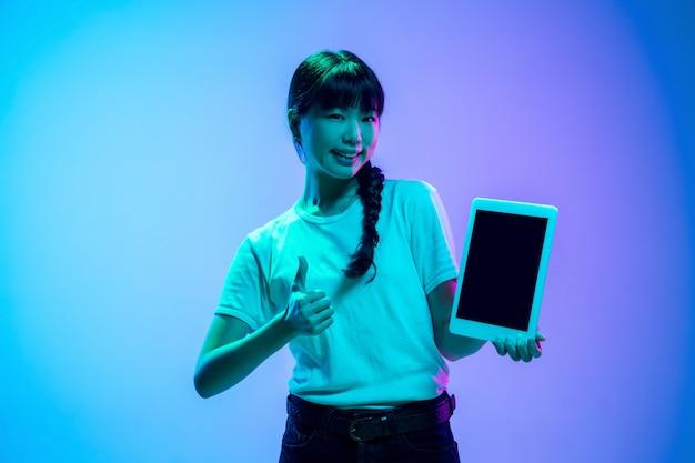 Mostrando a tela do tablet. retrato da jovem mulher asiática em fundo gradiente estúdio azul-roxo em luz de néon. conceito de juventude, emoções humanas, expressão facial, vendas, anúncio. bela modelo moreno.