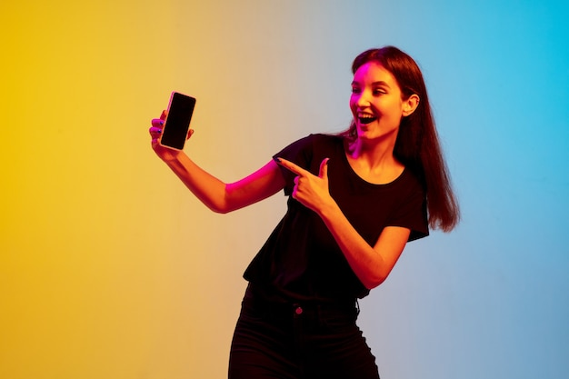 Mostrando a tela do telefone em branco. retrato de jovem mulher caucasiana em fundo gradiente estúdio azul-amarelo em luz de néon. conceito de juventude, emoções humanas, expressão facial, vendas, anúncio. linda modelo.