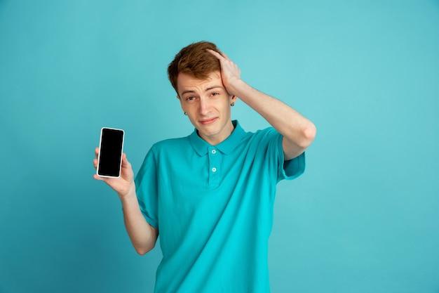 Mostrando a tela do telefone em branco. retrato moderno de jovem caucasiano isolado na parede azul, monocromático. lindo modelo masculino. conceito de emoções humanas, expressão facial, vendas, anúncio, moda.
