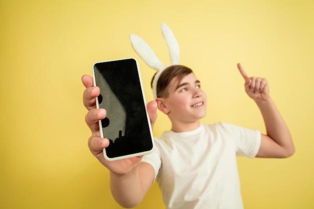 Mostrando a tela em branco, apontando para cima. menino caucasiano como um coelhinho da páscoa em fundo amarelo. saudações de páscoa feliz.