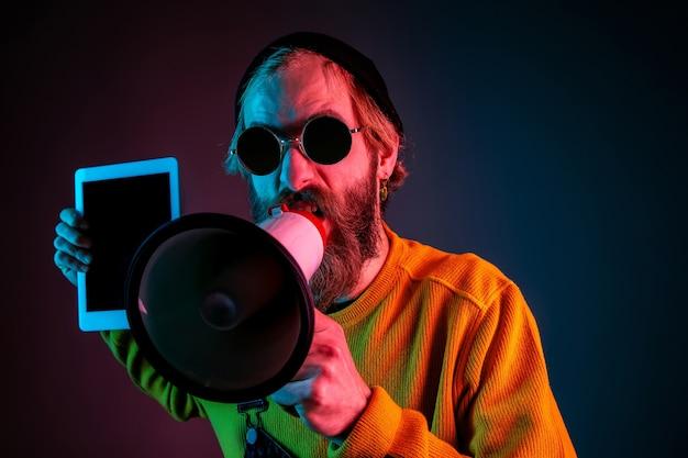 Mostrando a tela em branco do tablet. retrato do homem caucasiano em fundo gradiente de estúdio em luz de néon. lindo modelo masculino com estilo hippie. conceito de emoções humanas, expressão facial, vendas, anúncio.