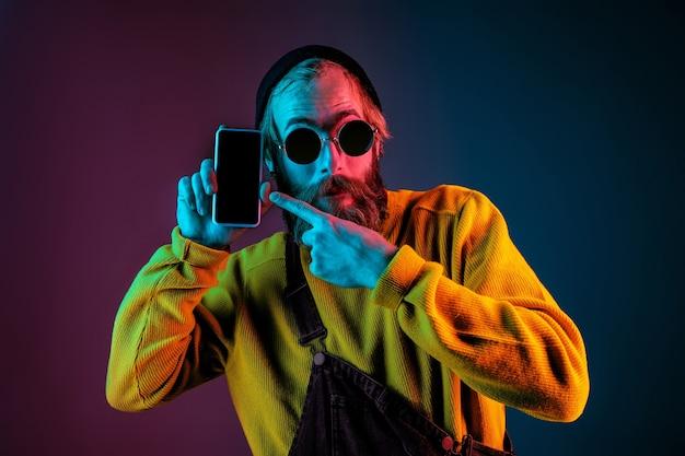 Mostrando a tela em branco do telefone. retrato do homem caucasiano em fundo gradiente de estúdio em luz de néon. lindo modelo masculino com estilo hippie. conceito de emoções humanas, expressão facial, vendas, anúncio.