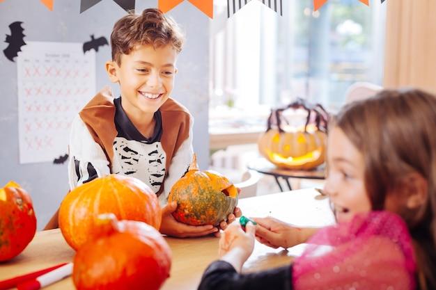 Mostrando abóbora. menino sorridente e feliz vestindo fantasia de esqueleto mostrando a pequena abóbora sua linda amiga de cabelos escuros Foto Premium
