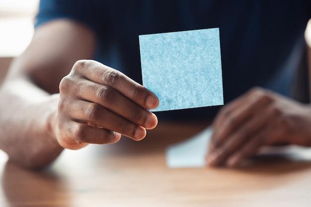 Mostrando adesivos em branco. perto das mãos masculinas afro-americanas, trabalhando no escritório. conceito de negócio, finanças, trabalho, compras ou vendas online. copyspace para publicidade. educação, freelance.