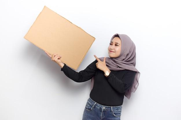 Mostrando cartaz de sinal em branco para inscrição e texto de jovens lindas mulheres muçulmanas asiáticas vestem hijab