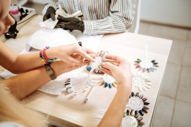 Mostrando cor. filha elegante e fofa usando pulseiras brilhantes mostrando as melhores cores de goma-laca