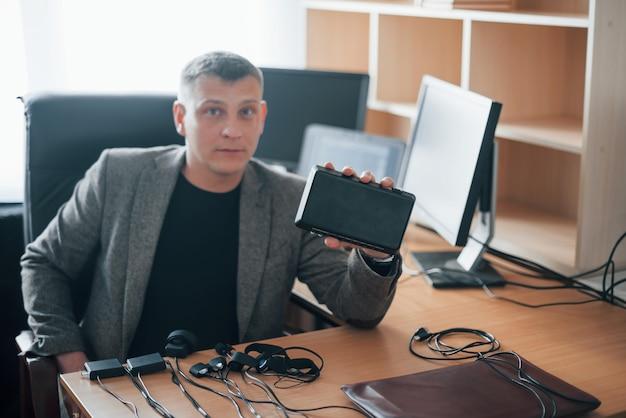 Mostrando dispositivo. o examinador de polígrafo trabalha no escritório com seu equipamento detector de mentiras