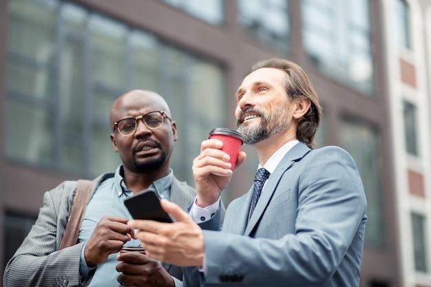 Mostrando e-mail. homem de negócios maduro de cabelos grisalhos mostrando e-mail para o funcionário pela manhã