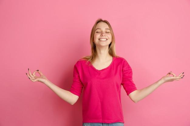 Mostrando feliz e brilhante. retrato de mulher jovem branca isolado na parede rosa, monocromático. linda modelo feminino. conceito de emoções humanas, expressão facial, vendas, anúncio, moda.